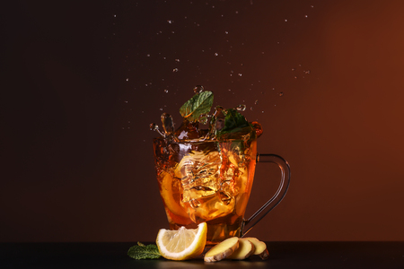 Glass cup and splash of delicious lemon tea with ginger on table against color background