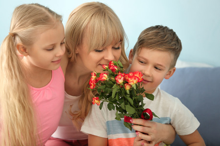 Cute little kids congratulating their mother at home