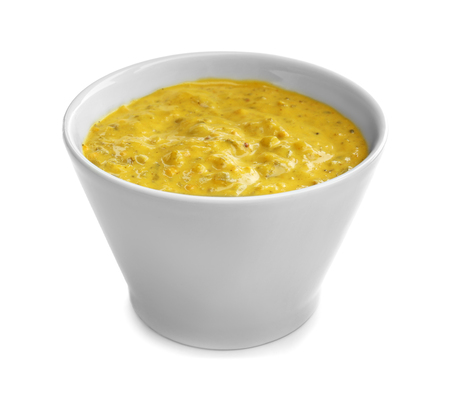 Tasty yellow sauce in bowl on white background