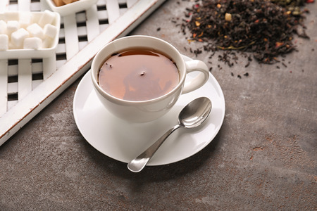 Ceramic cup with aromatic tea on table