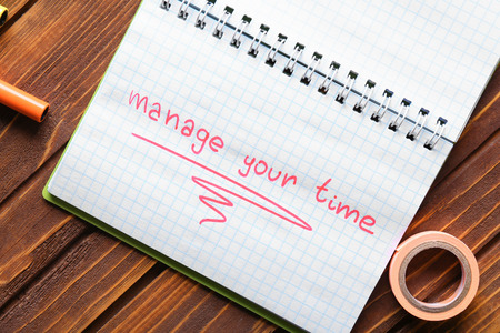 Notebook with phrase MANAGE YOUR TIME on wooden table