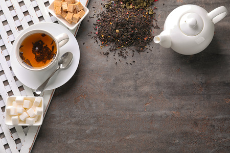 Flat lay composition with dry tea leaves, sugar and hot beverage on grey background 免版税图像