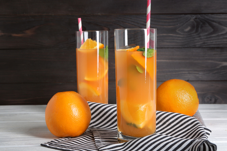 Glasses with fresh citrus juice on table