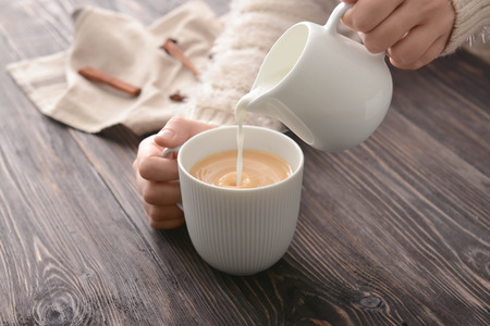 Woman pouring milk into cup of tea on table Imagens