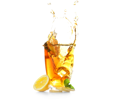 Glass and splash of delicious lemon tea with ginger on white background