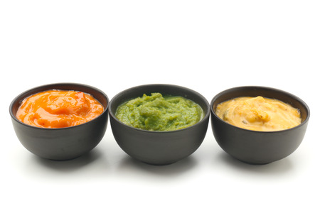 Different tasty sauces in bowls on white background Imagens