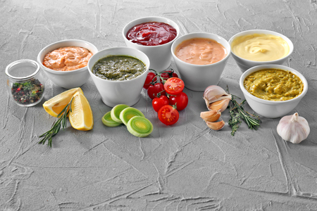 Different tasty sauces in bowls on grey background