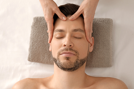 Handsome man having head massage in spa salon Stok Fotoğraf