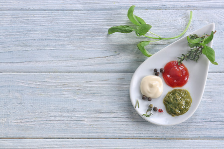 Plate with tasty sauces and herbs on light wooden table Imagens