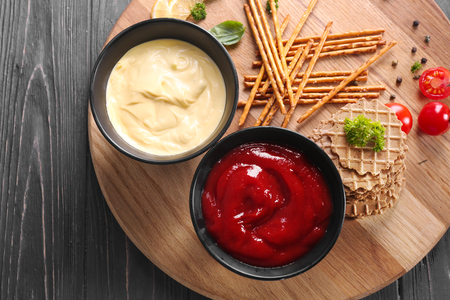 Tasty sauces in bowls with snacks on wooden board Imagens