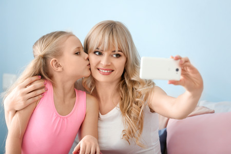 Cute little girl and her mother taking selfie at home