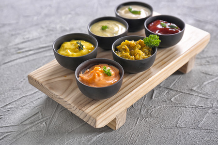 Different tasty sauces in bowls on wooden board