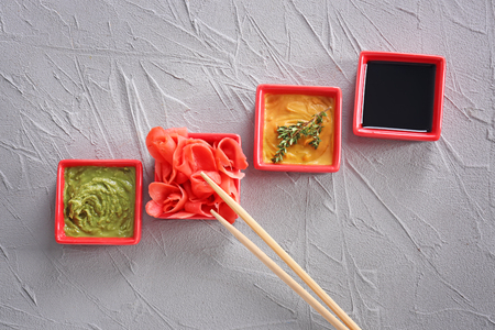 Different tasty sauces with marinated ginger in bowls on grey background
