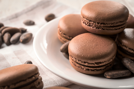 Tasty chocolate macarons on plate, closeup 免版税图像