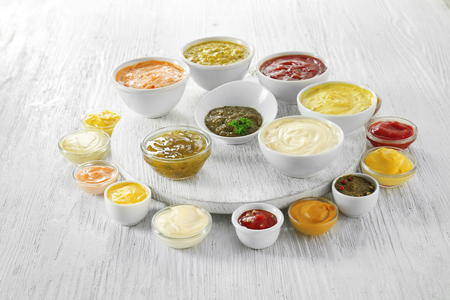 Different tasty sauces in bowls on white wooden table