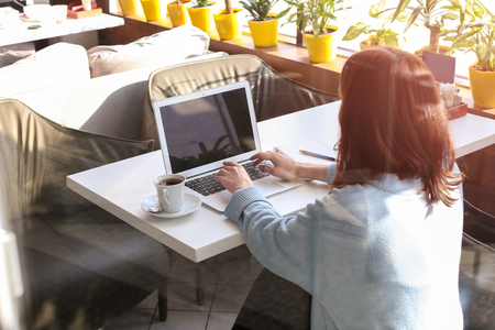Young woman using laptop in cafe, view through window