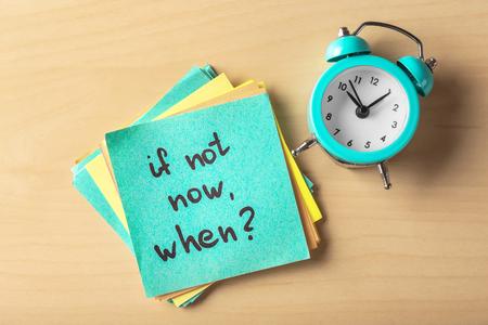 """Naklejka z napisem """"Jeśli nie teraz, to kiedy?"""" i budzik na stole. Koncepcja zarządzania czasem"""