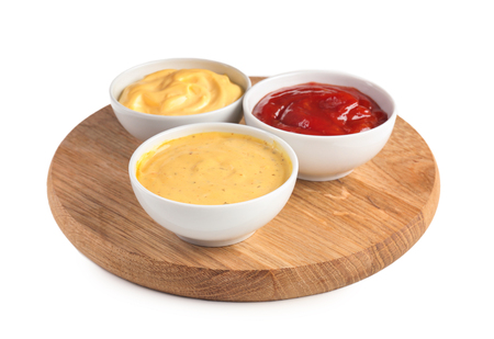 Wooden board with tasty sauces in bowls on white background