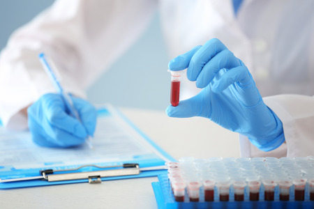 Woman working with blood sample in test tube at table