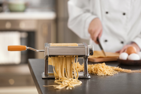 Pasta maker with dough and blurred chef on background 免版税图像