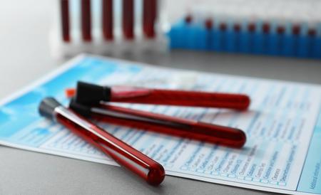Tubos de ensayo con muestras de sangre y forma en mesa