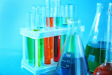 Chemical glassware with colorful samples on color background Stock Photo