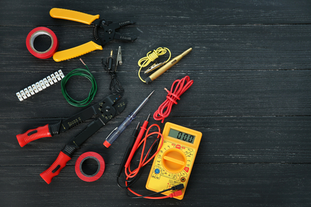 Flat lay composition with electrical tools on wooden background Фото со стока