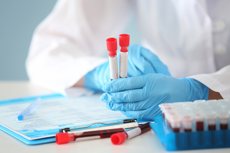Woman working with blood samples in test tubes at table