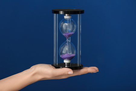 Woman holding hourglass on color background. Time management concept Reklamní fotografie