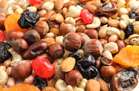 Different nuts, dried fruits and berries as background