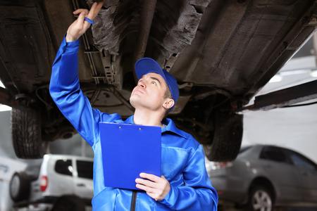 Mécanicien masculin avec presse-papiers examinant la voiture dans le centre de service