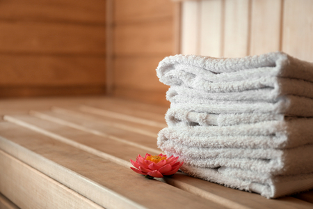Stack of towels on wooden bench in sauna 免版税图像