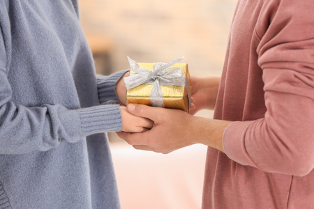 Young loving couple with gift box at home, closeup Banque d'images