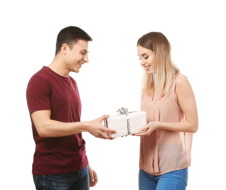 Young man giving present to his beloved girlfriend on white background 免版税图像
