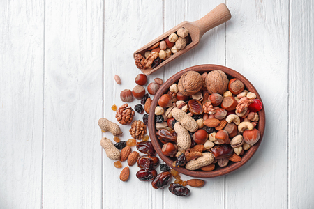 Flat lay composition with different nuts and dried fruits on wooden table