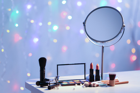 Set of decorative cosmetics with brushes on table against blurred lights
