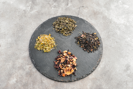 Slate plate with different types of dry tea on grey background Imagens