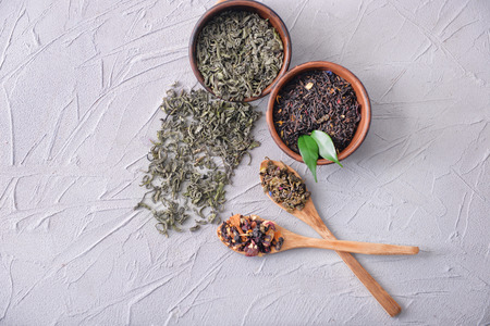 Flat lay composition with different types of dry tea leaves on light background