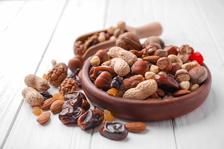 Plate with different nuts and dried fruits on wooden table