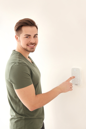 Young man entering code on security alarm system, indoors