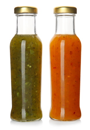 Bottles with tasty sauces on white background