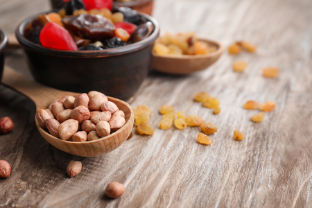 Composition with peanuts and dried fruits on wooden background Banque d'images