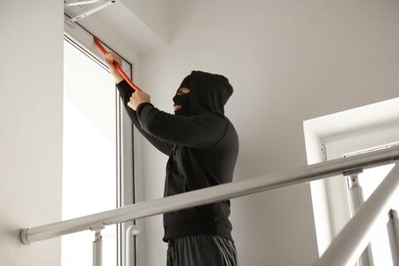 Burglar trying to open door with crowbar, indoors