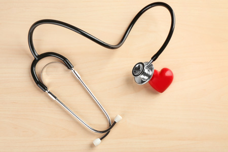 Stethoscope with small heart on wooden background