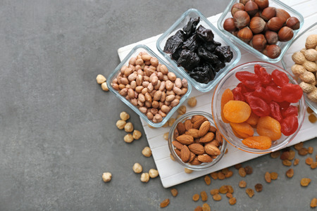 Different kinds of nuts and dried fruits in bowls on table Stockfoto