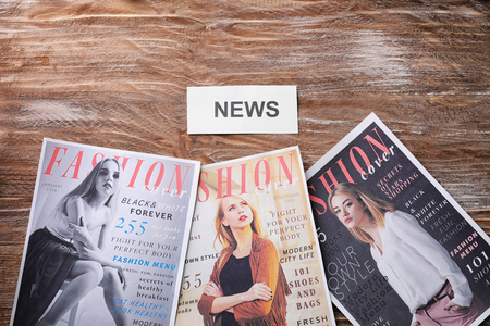 Paper with word NEWS and fashion magazines on wooden background