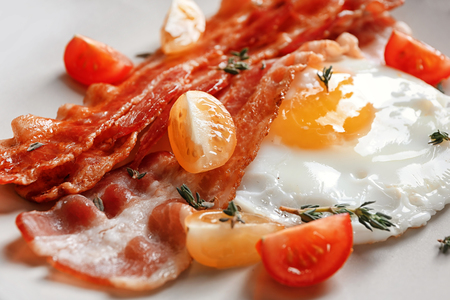 Plate with tasty bacon and fried egg, closeup