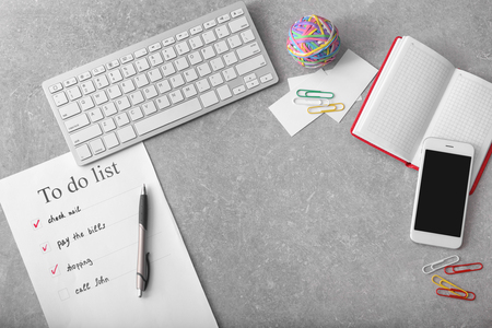 Composition with to-do list and computer keyboard on grey background