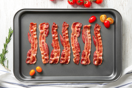 Baking sheet with tasty bacon on table