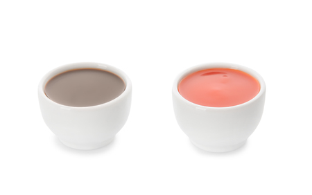 Two bowls with tasty sauces on white background